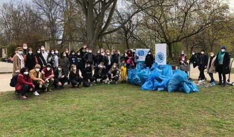 Students of Net Impact in a group photos with masks on and full trash bags beside them.